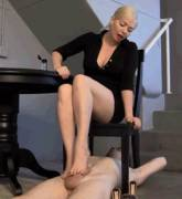 She's in a chair playing with him using her bare feet