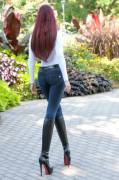 Redhead, jean and black boots from rear view